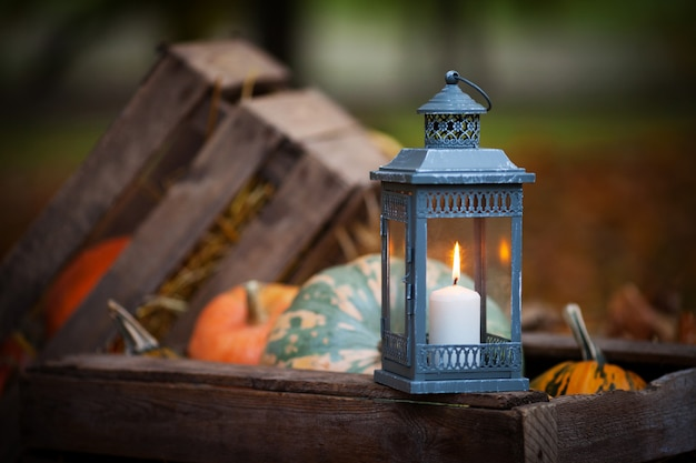 Grey lantern with burning candle on wooden box decorated in autumnal style