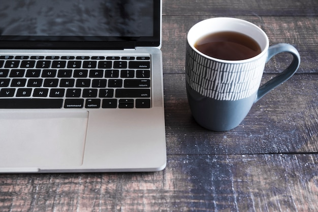 Grey laptop with coffee on wooden table