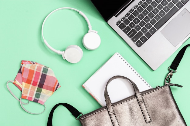 学用品、ラップトップ、コピーブック、白いヘッドフォン、紙の感染から保護するためのマスクが付いたグレーのレザーバックパック。学校のコンセプトに戻る。クローズアップ、コピースペース、フラットレイアウト。