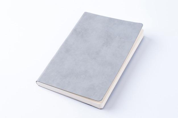 白い背景にある灰色の革のノート