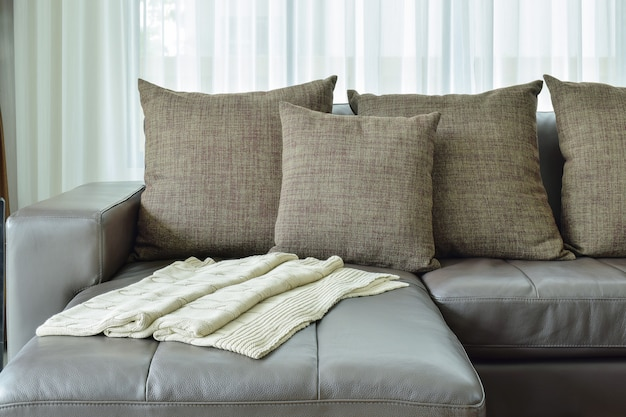 Grey leather sofa with texture brown pillows in modern living room
