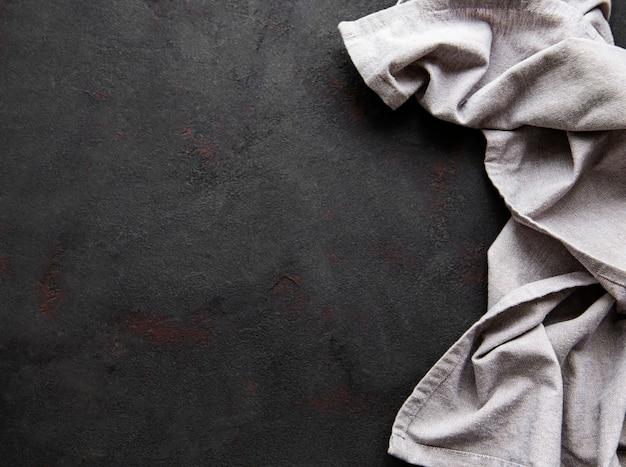 黒の背景のカウンタートップに灰色のリネンのテーブルクロス。上面図。