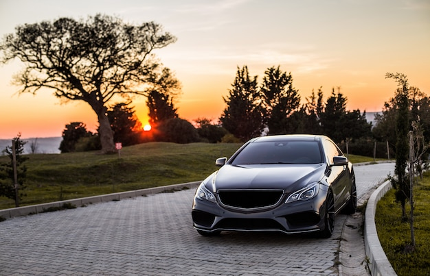 A grey luxury sedan car in the sunset.