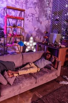 灰色の乱雑なコーチ。大音量のアルコールパーティーの後、汚れた汚れたソファで休んでいる二日酔いのアフリカ系アメリカ人の男