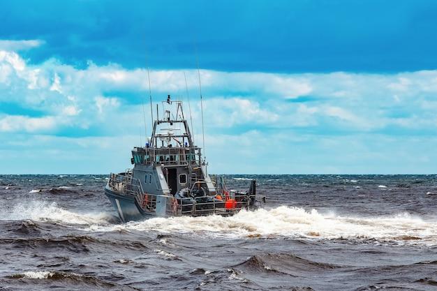 Серый военный корабль плывет в балтийском море. пограничная служба