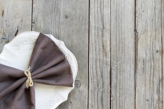 Серая салфетка на тарелку на деревянный стол сверху с копией пространства