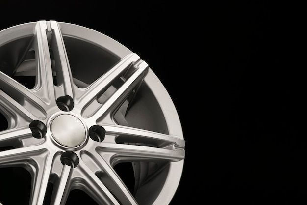 Grey new alloy wheel for car, side view close-up, polished. copyspace