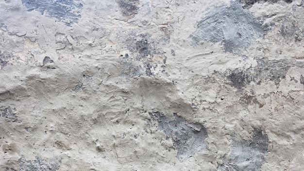 灰色の塗装とひびの入ったレンガの壁のテクスチャ