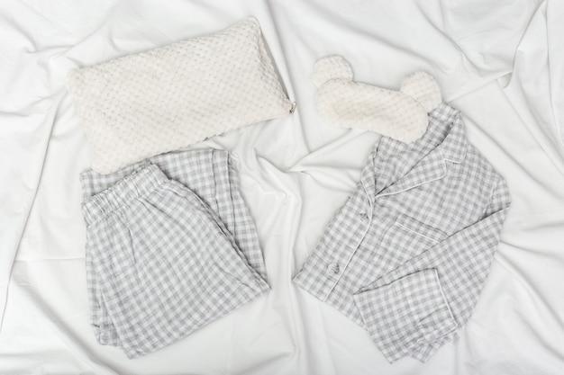 Grey pajamas, sleep mask, soft fluffy cushion on white crumpled sheet.