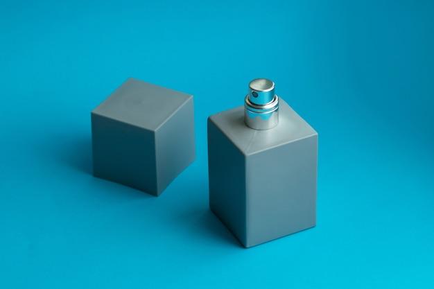 紙の背景に灰色の香水瓶