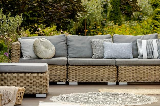 Grey pillows on trendy wicker l shape sofa in the green garden