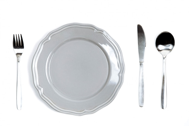 A grey plate with silver fork, spoon and knife isolated on white