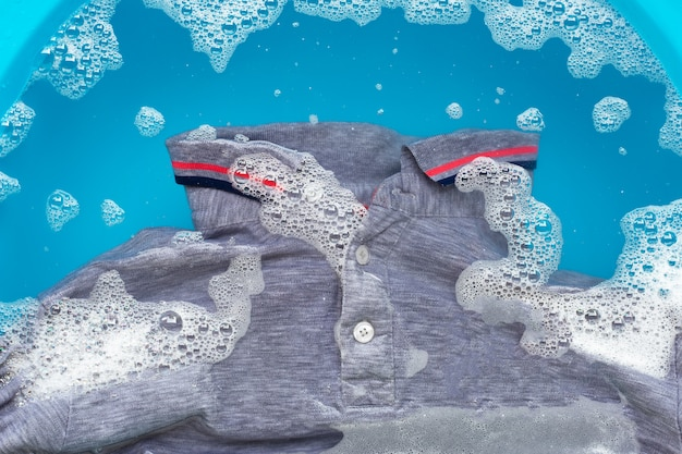 Grey polo shirt soak in powder detergent water dissolution. laundry concept