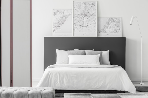 Grey pouf in elegant bedroom interior with maps on black bedhead of white bed