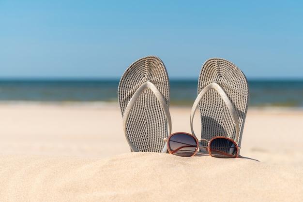 美しい晴れた日のビーチで灰色のサンダル。海沿いの砂の中のスリッパ。海沿いの海岸でフリップフロップ。