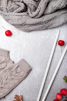Grey scarf, hat gloves near knitting needles on grey surface,