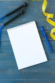 灰色のスニーカー、青いダンベル、空白のメモ帳、白い背景の上の青いペン上面図