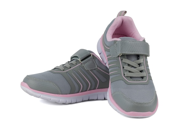 Grey sneakers with pink lining isolated on white surface