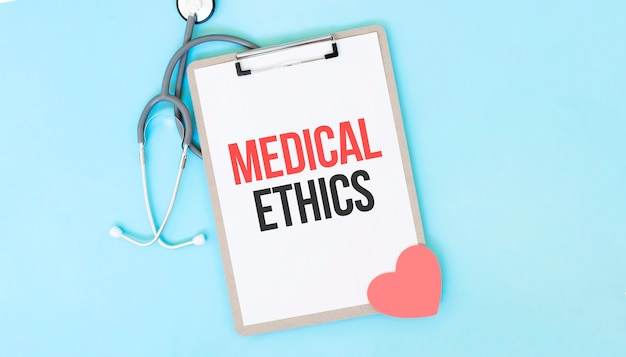 Grey stethoscope and paper plate with a sheet of white paper with text medical ethics light blue backround. medical concept.