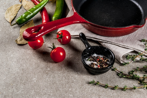 Grey stone culinary background with empty black pan and selection of spices and seasonings