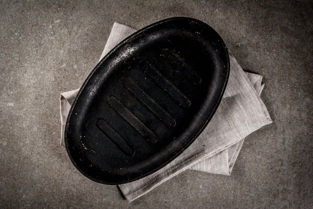 Grey stone culinary background with empty black pan