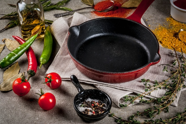 Grey stone culinary  with empty black pan and selection of spices and seasonings, top view
