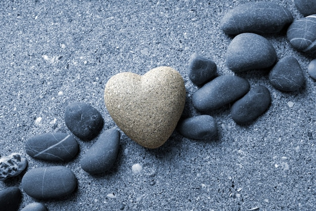 砂の表面にハートの形をした灰色の石