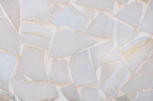 背景に白いセメントが付いた灰色の石