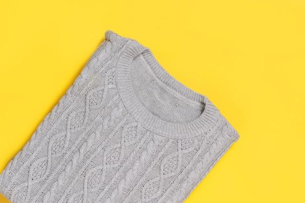 Серый свитер на желтом виде сверху