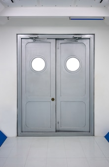 Grey swing doors with circlie windows and automatic hydraulic leaver hinge door.