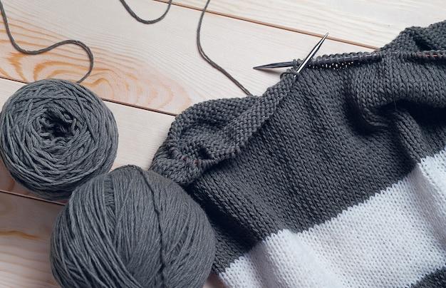 Серые нитки, мотки и клубки итальянской шерстяной пряжи.