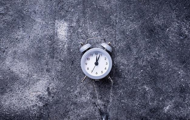 Grey vintage alarm clock on concrete table
