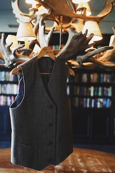Grey waistcoat for a gentleman hangs on the peg with lettering groom