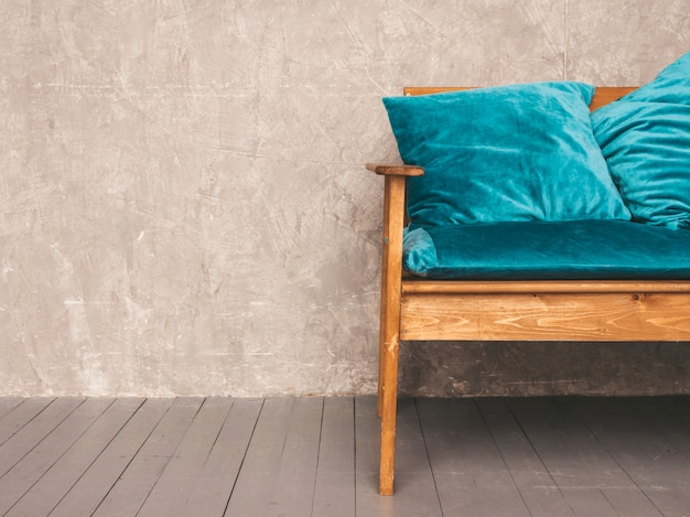 Grey wall interior with stylish upholstered blue and wooden modern sofa
