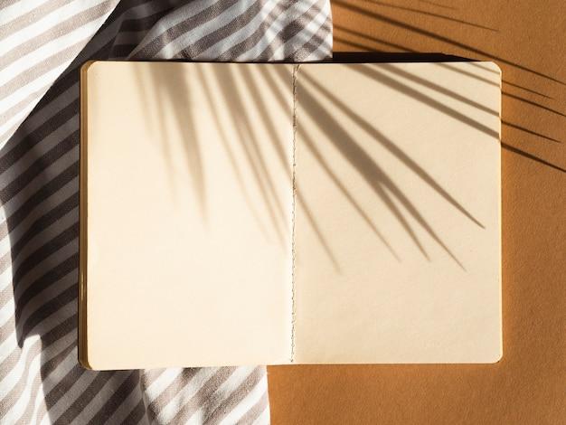 Spazio in bianco spogliato grigio e bianco su un fondo beige con l'ombra di foglia di palma