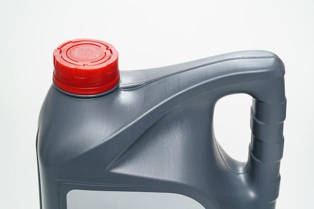 흰색 배경에 기계 오일이 있는 빨간색 뚜껑 용기가 있는 회색. 움직이는 엔진 부품 사이의 마찰을 줄이기 위한 모터 오일. 자동차 서비스 및 상점