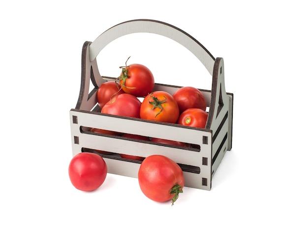 흰색 배경에 분리된 회색 나무 상자와 잘 익은 빨간 토마토.