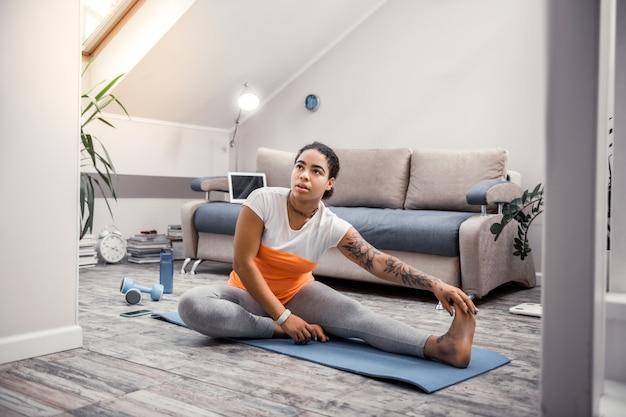 灰色の木の床。アクティブでありながらオレンジ色の要素を持つ快適なスポーツ服を着ているアフリカ系アメリカ人の女性