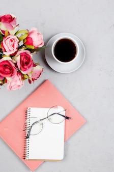 Серый рабочий стол с блокнотами, пустой бланк, принадлежности, стаканы и чашка кофе