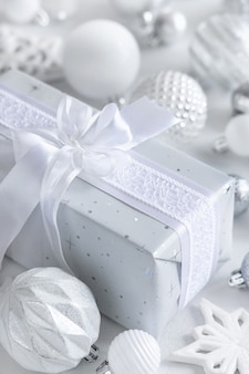 Grey wrapped present with a white bow and white and silver christmas decorations closeup. winter composition with blank label card, mockup, copy space