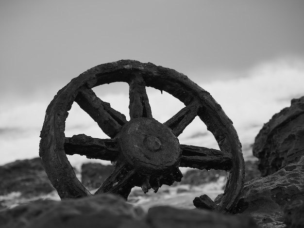 Primo piano in scala di grigi di una vecchia ruota arrugginita circondata da pietre