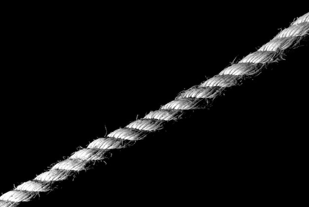 Greyscale closeup of a rope under the lights against a black background