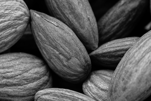 Greyscale closeup shot of a lot of almonds