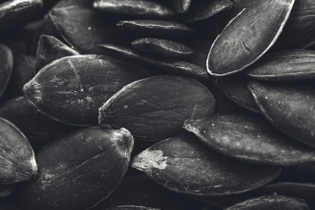 Colpo di primo piano in scala di grigi di un sacco di semi di zucca - ottimo per uno sfondo bianco e nero