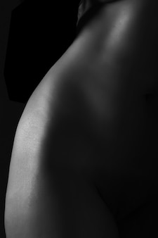 Greyscale closeup shot of a naked woman's waist on the black