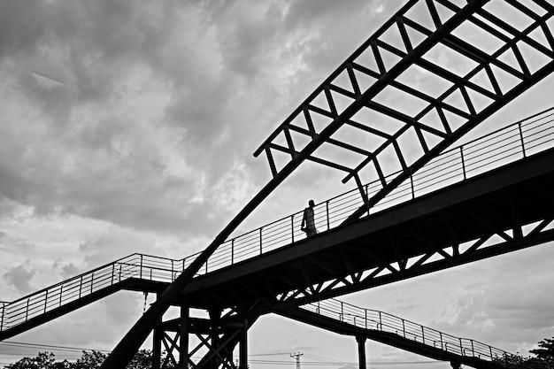 Greyscale low angle shot of a male walking through a bridge