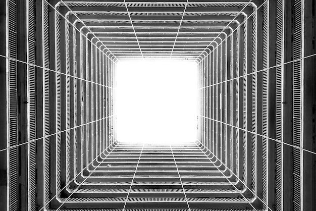 高層ビルの天井から差し込む光のグレースケールローアングルショット