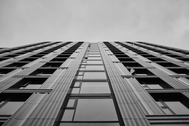 Greyscale of a modern skyscraper under the cloudy sky