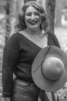 森の中で帽子をかぶった笑顔の女性のグレースケール