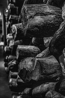 Greyscale photo of pile of logs